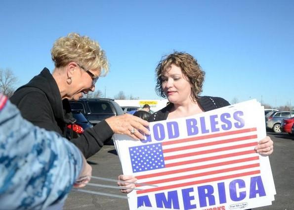 handing out god bless america signs pittsburg kansas